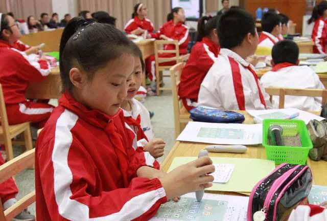 学生们在课堂上使用焦点智慧教室点读笔板与老师进行互动反馈
